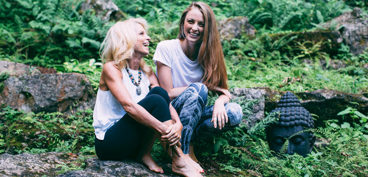 Kelly Childs and Erinn Weatherbie on vacation sitting in a forest smiling