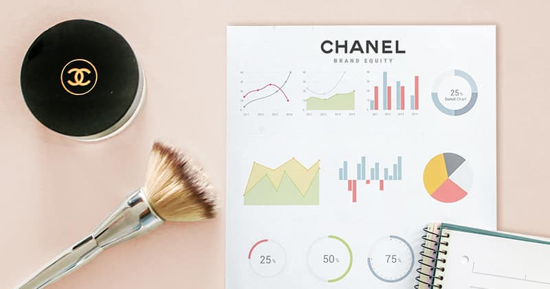Chanel make up, Chanel make up brush, charts of brand equity for Chanel, and a notebook.