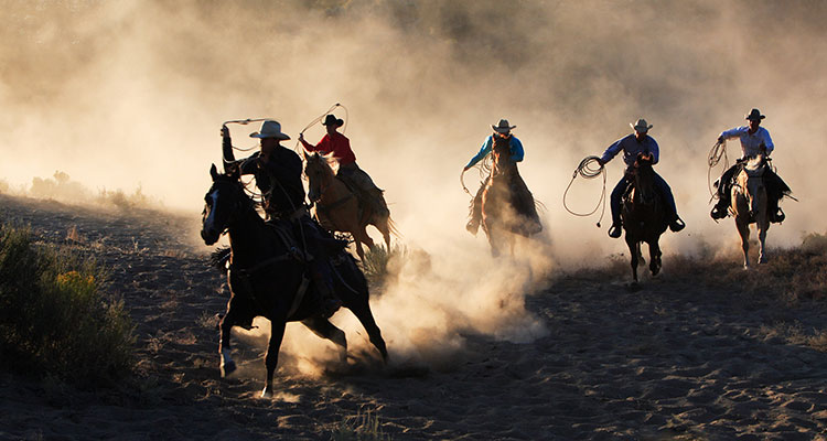 Five cowboys on horseback traveling through a dusty field at dusk.