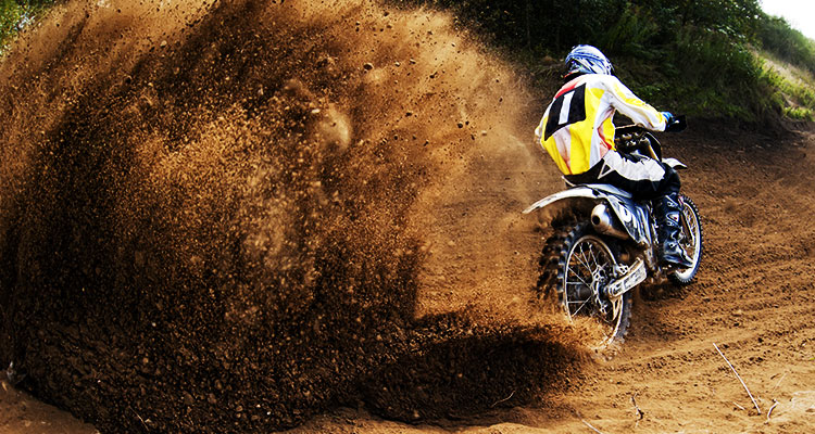 A motocross biker trowing up a large trail of dirt from his rear wheel