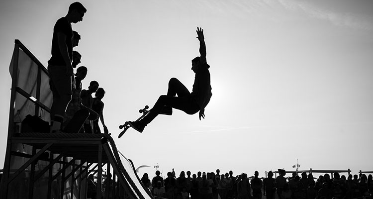 A skateboarder making a jump at the top of a half pipe.
