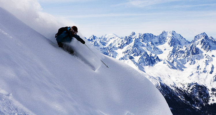 A skier coming down a mountain in fresh powder