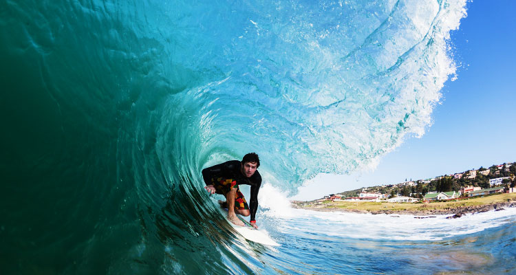 A surfer in the middle of the barrel of a wave off of a sandy beach with cottages