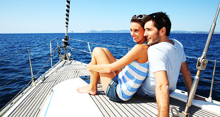 A couple on a sailboart with mountain islands in the background