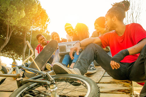 Group of friends sitting with the bikes and skateboards.