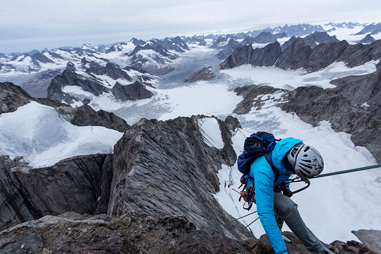 A climber in a blue Arc'teryx brand jacket in front of an amazing mountain range vista