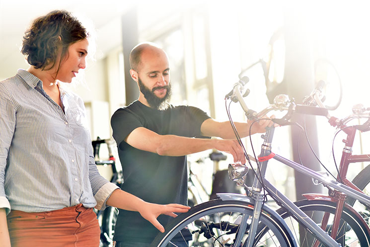 A bike shop owner with a beard showing a woman a bike.