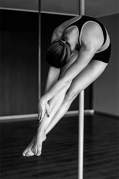 Tall woman performing a hold at a pole dance studio.