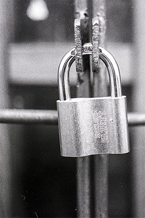 Padlock on a metal gate. Black and white.