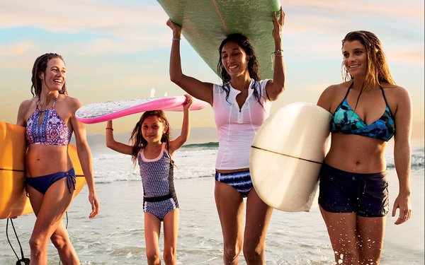 Four ladies at the beach with surfboards