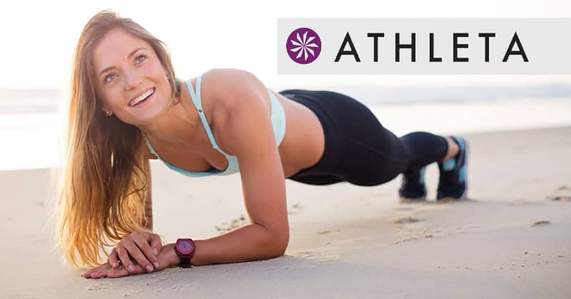 Athleta. Woman doing a plank on the beach.