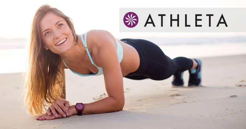 Athleta. Woman doing a plank on the beach.
