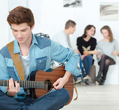 Young man playing a guitar and a group of teens in the backgrounds.
