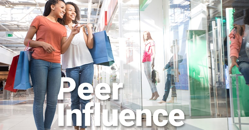 Teen girls who are best friends looking into a store window at a mall and pointing to an item of clothing.