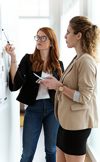 Two professional women discussing design choices for a brand.