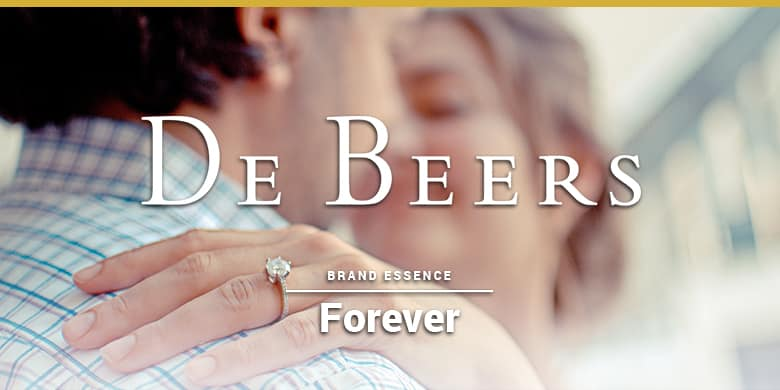 De Beers brand essence is forever. Woman with diamond ring hugging a man.
