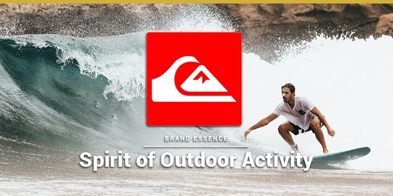 Quiksilver's brand essence is spirit of outdoor activity. Man surfing on rocky beach.