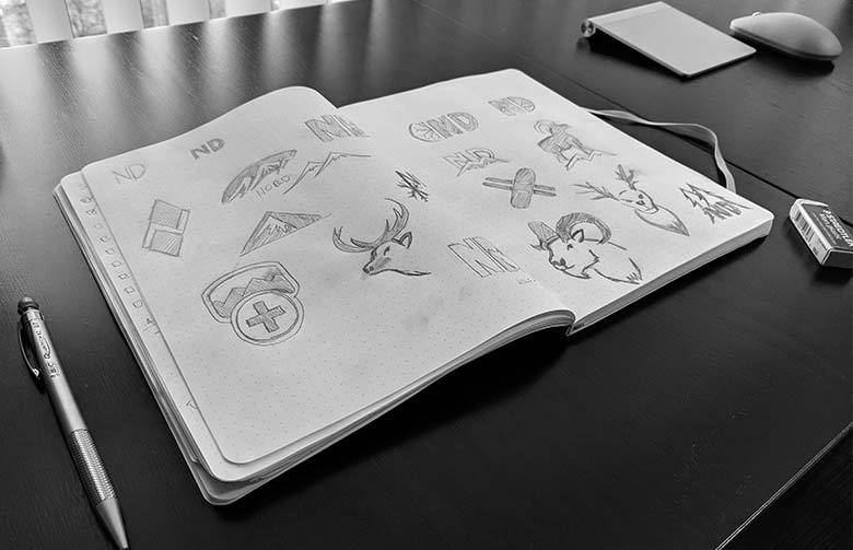 Graphic designers sketchbook with winter themed logo concepts for a ski lifestyle brand logo.