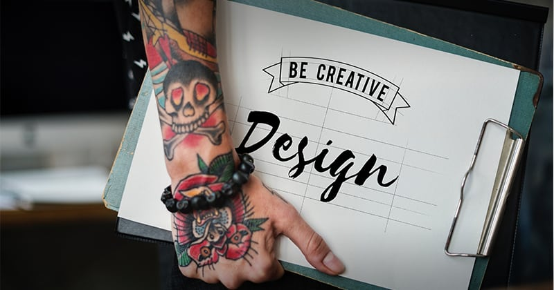 "Tattooed arm holding design. Design says ""be Creative: design"""