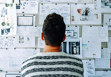 Man standing in front of brainstorming ideas.