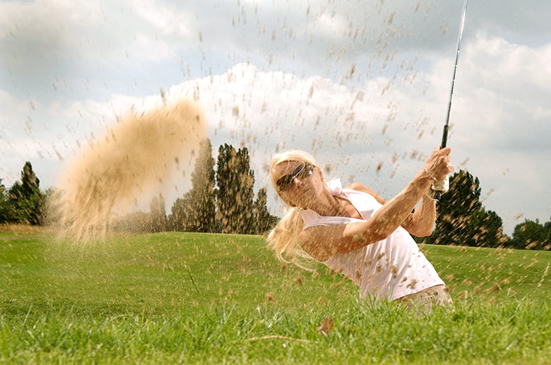 Woman golfer pitching out of the sand trap.