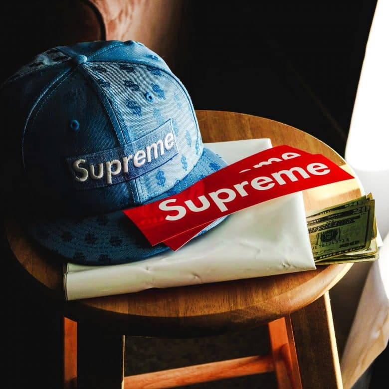 Supreme baseball cap. Supreme stickers. Money.