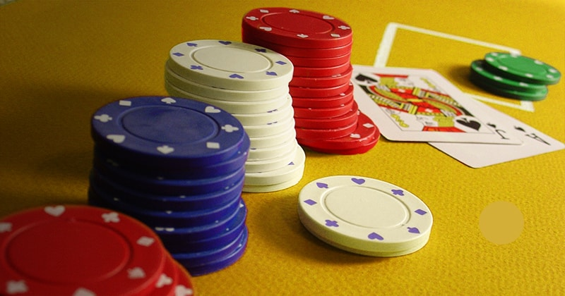 Poker chips and poker card on gold poker table.