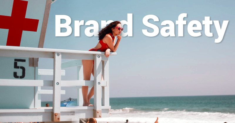 Lifeguard on a lifeguard tower overlooking a beach. The words brand safety behind her.