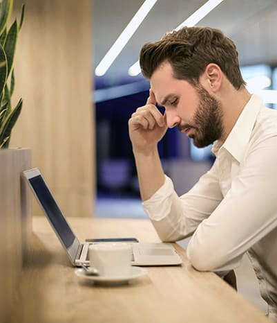 Brand marketer looking concerned leaning over his desk looking at his computer.