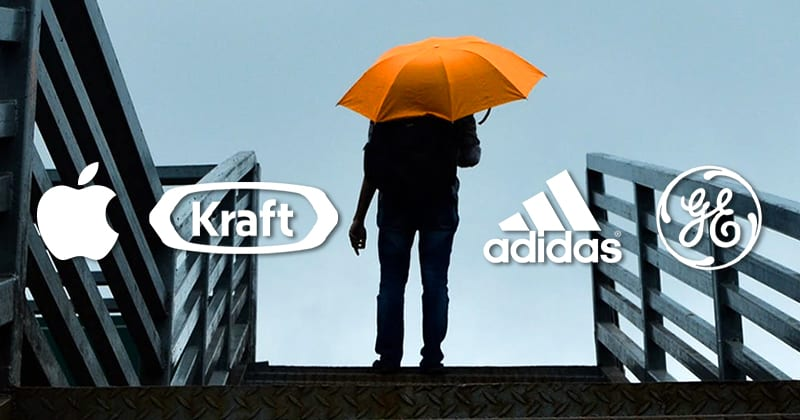 Person standing at the top of a set of stairs holding an orange umbrella. Apple, Kraft, Adidas and GE logos.