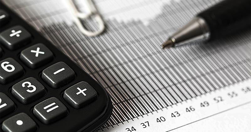 Asset on financial records. Calculator, pen and paperclip
