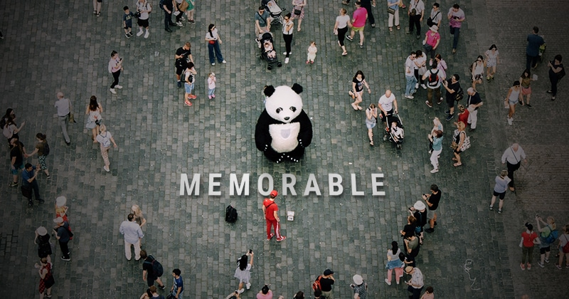 "Person in a panda suite standing in front of the word ""memorable"" in a crowd."