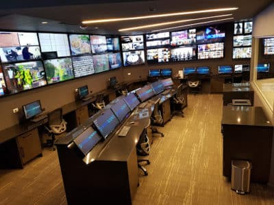 Control room at MediaScience Lab. Wood floor, arch desk with monitors, monitors on the wall.