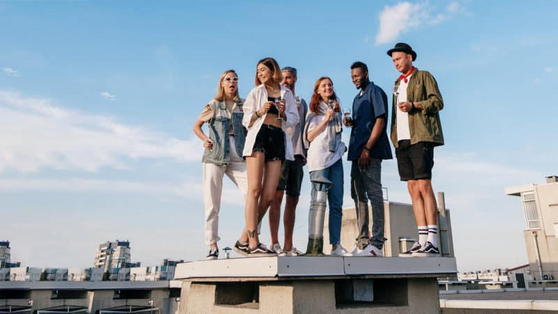 Teens on a roof looking at the view because of peer influence.